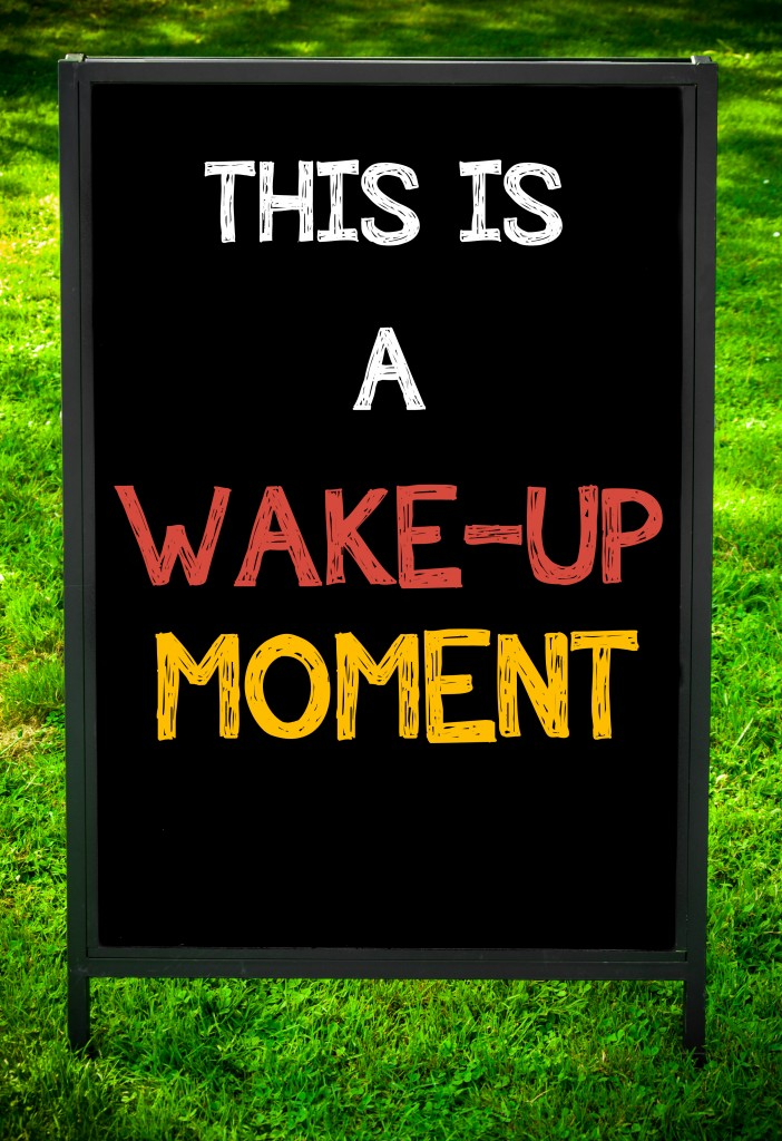 THIS IS A WAKE-UP MOMENT message on sidewalk blackboard sign against green grass background. Copy Space available. Concept image